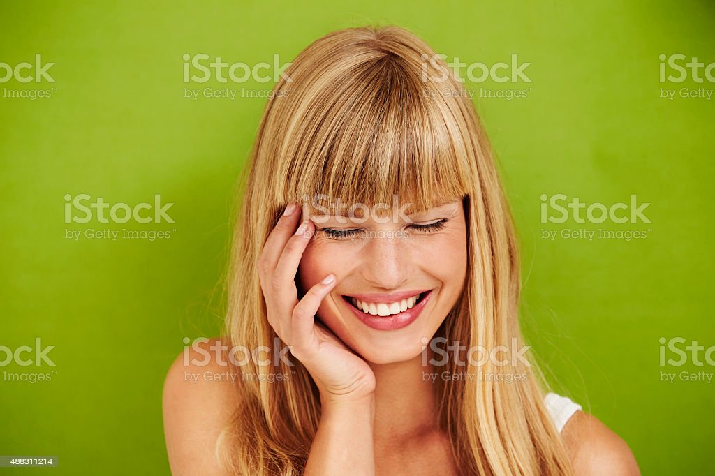 Joyful woman laughing on green background