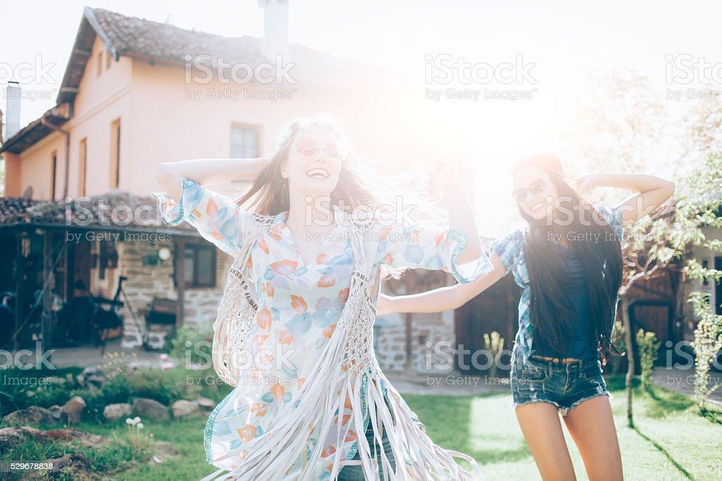 Joyful women with daisies wreath dancing stock photo