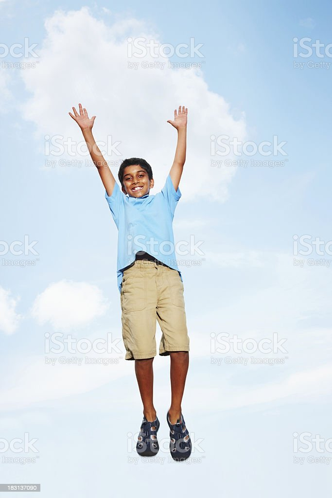 Joyful young boy jumping with arms outstretched against sky royalty-free stock photo