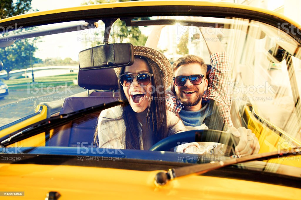 Joyful young couple smiling while riding in onvertible stock photo