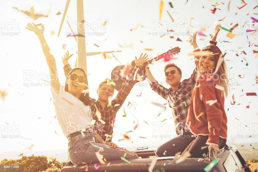 Joyful young friends enjoying the outdoor party together with confetti in nature stock photo