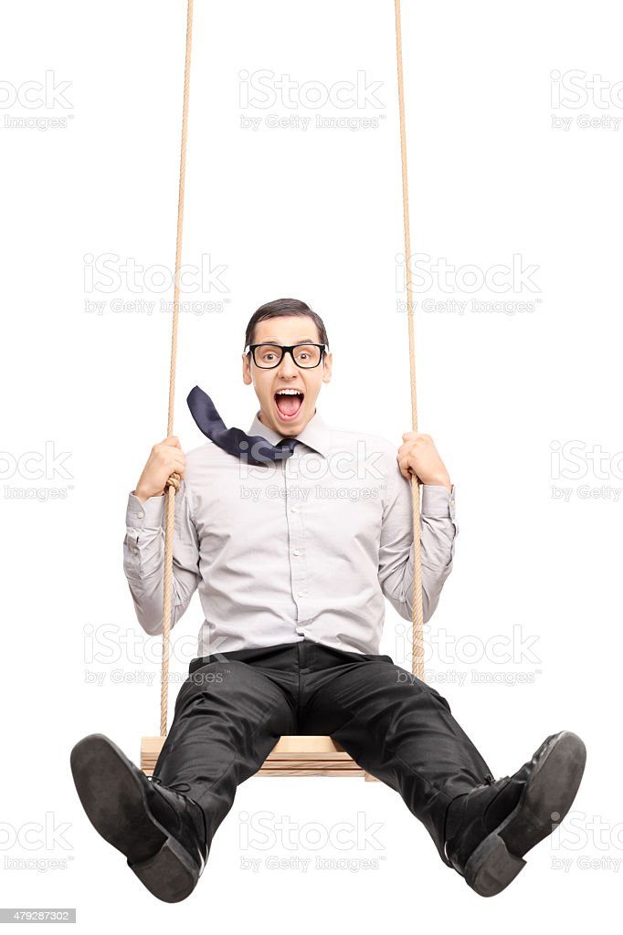 Joyful young guy swinging fast on a swing stock photo