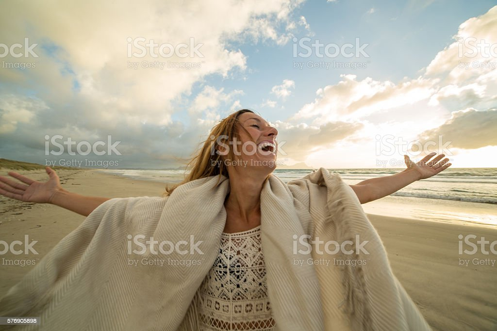 Joyful young woman arms outstretched on beach at sunset stock photo