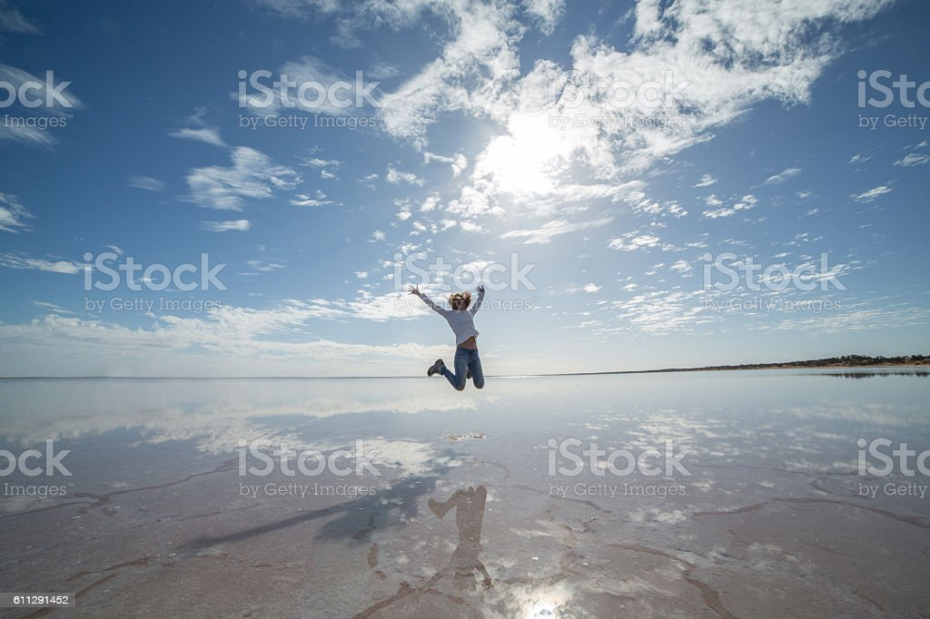 Joyful young woman jumping mid-air on salt lake stock photo