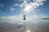 Joyful young woman jumping mid-air on salt lake