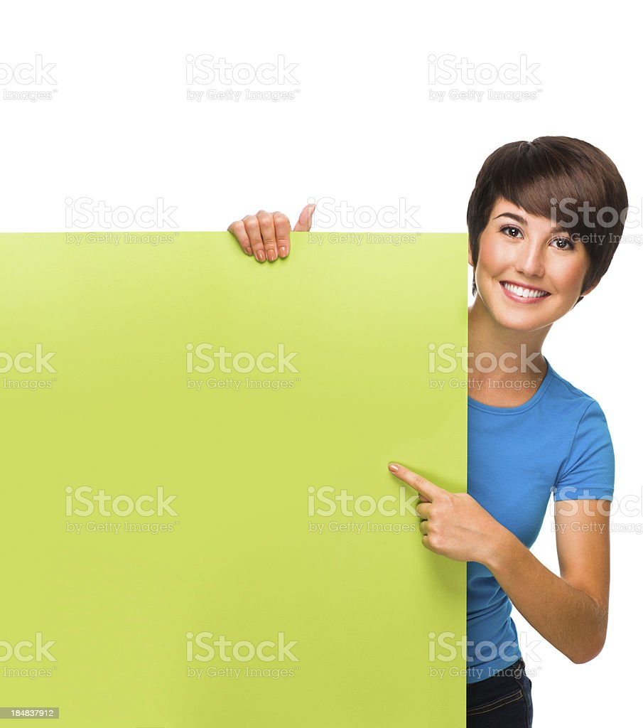 Joyful young woman pointing at a sign royalty-free stock photo