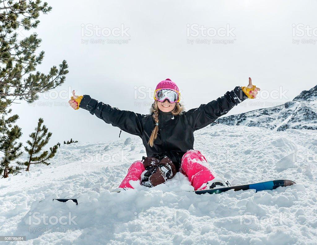 Joyful young woman snowboarder stock photo