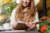 Joyful young woman studying in cafe