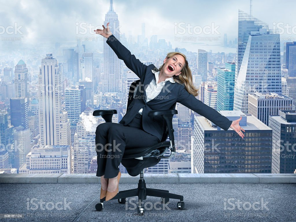 Joyous Businesswoman Sitting In Chair On Top Of Tall Building stock photo