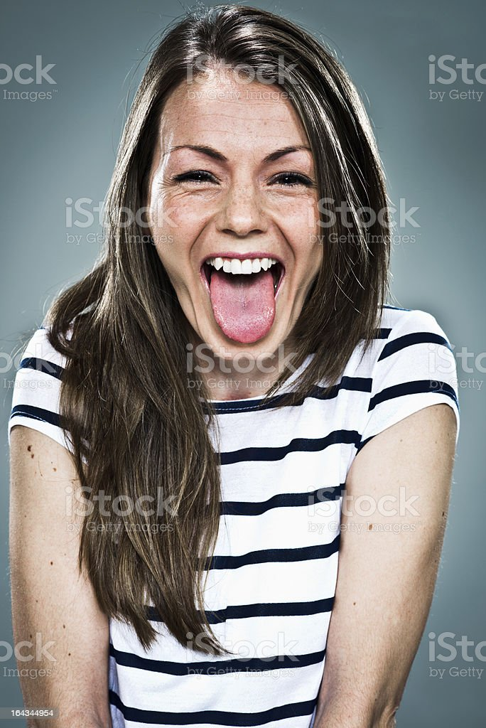 Joyous young woman in striped top sticking out her tongue stock photo
