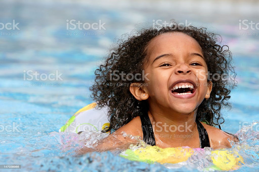 A jubilant kid swimming in a pool stock photo