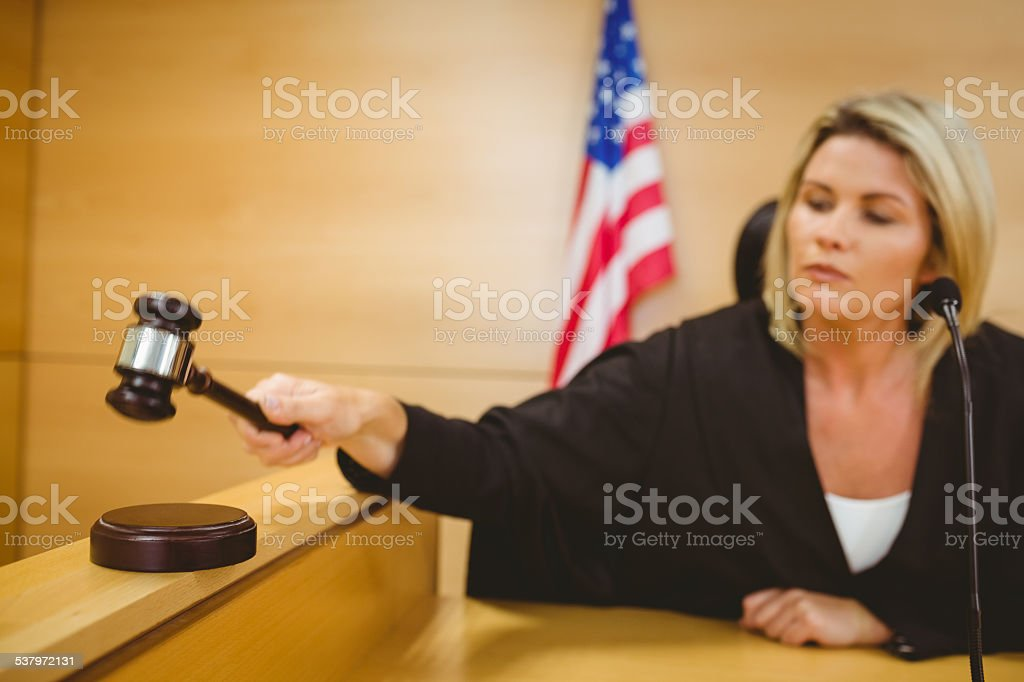 Judge about to bang gavel on sounding block stock photo