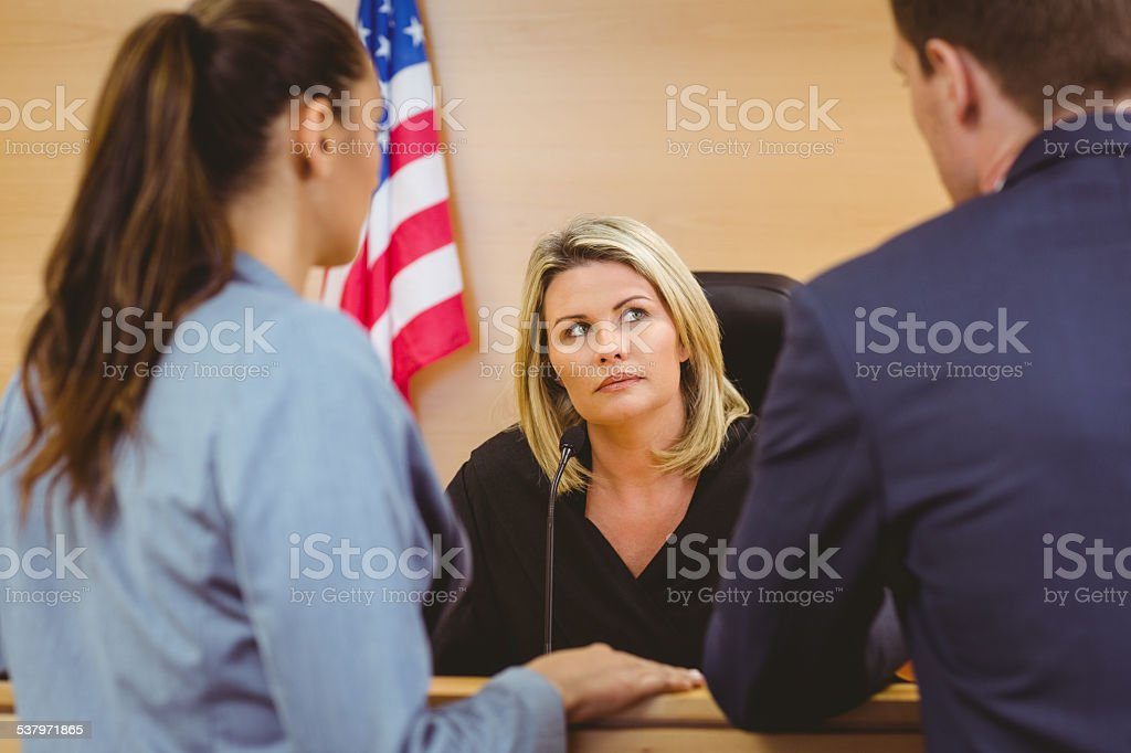 Judge and lawyers speaking in front of the american flag stock photo