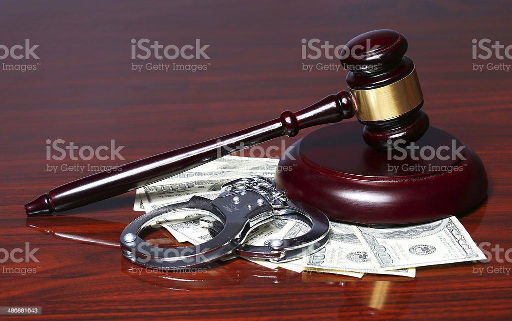 Judge Gavel and Handcuffs with Dollars Bills on Table. stock photo