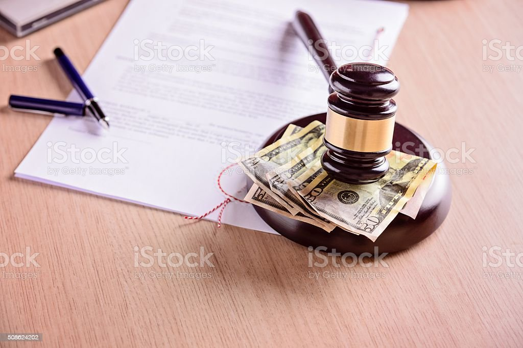 Judge gavel and money next to judgement on wooden table. stock photo