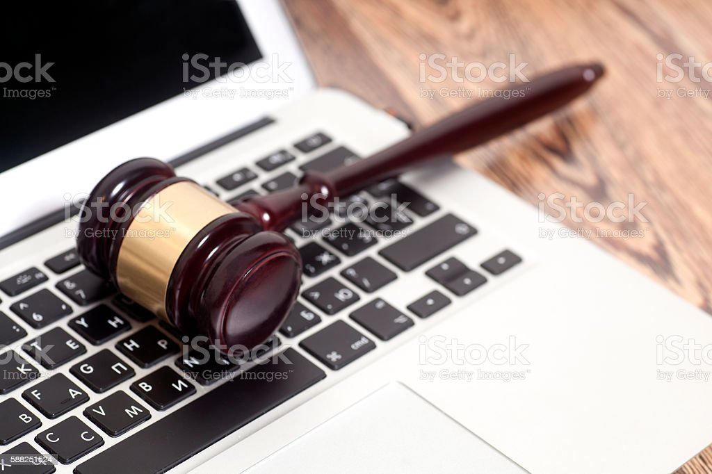 Judge gavel with laptop computer on wooden background stock photo