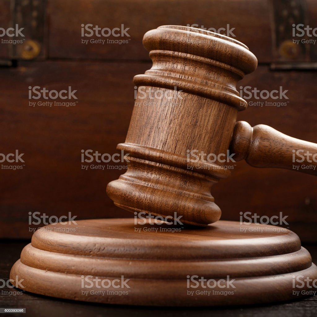 Judge hammer on brown wooden background stock photo