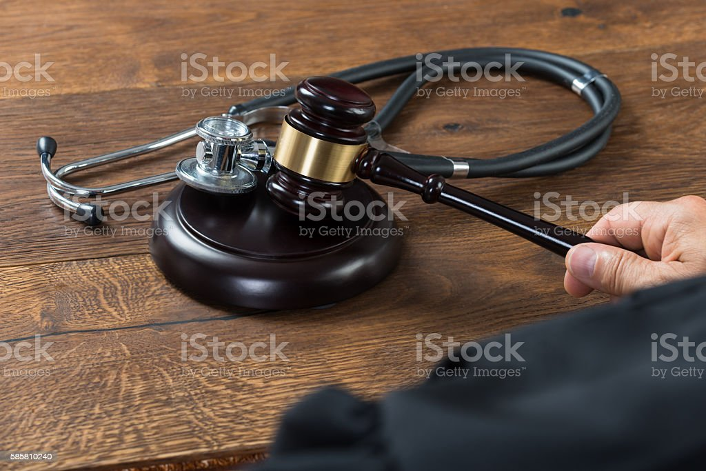 Judge Hitting Gavel With Stethoscope In Courtroom stock photo