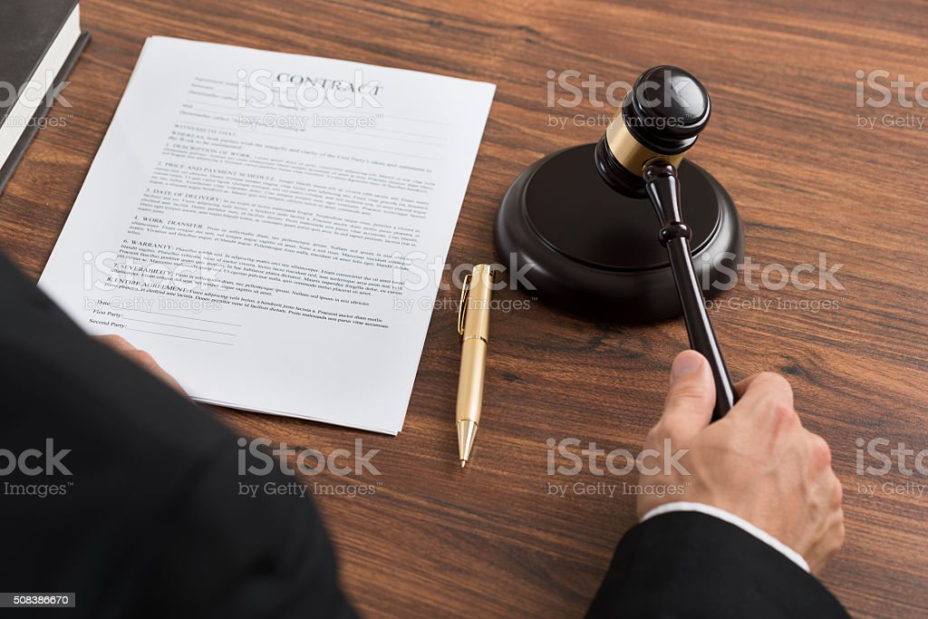 Judge Hitting The Gavel At Desk stock photo