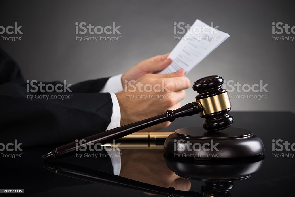 Judge Holding Document At Desk stock photo