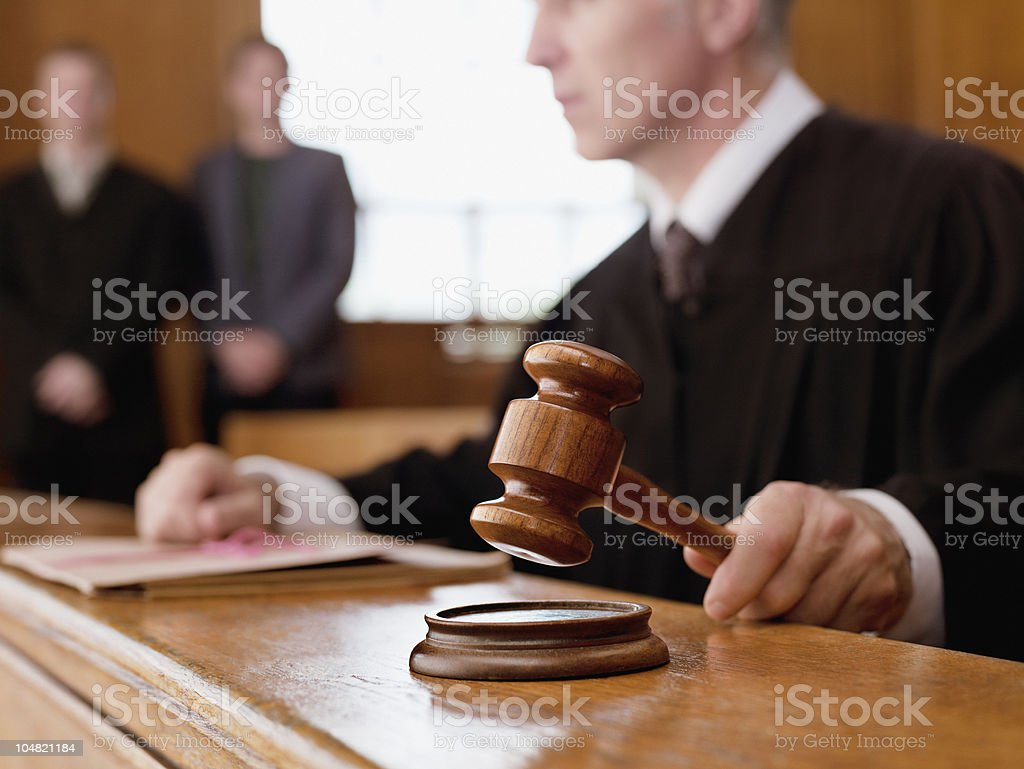 Judge holding gavel in courtroom stock photo