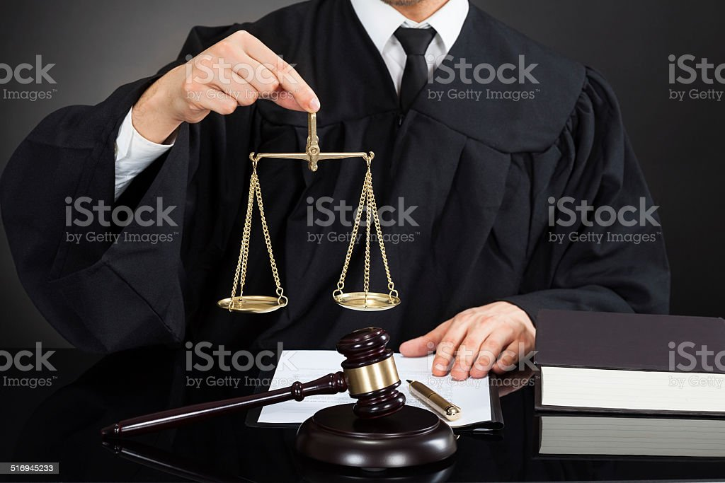 Judge Holding Weight Scale At Desk stock photo