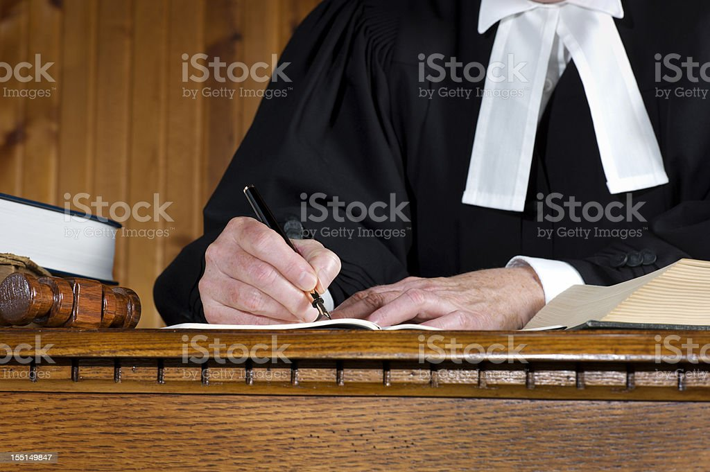 Judge in robes Taking Notes. stock photo