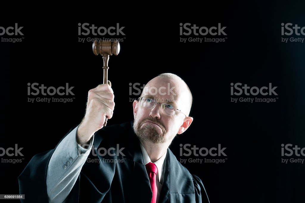 Judge looks at the court hammer in court stock photo