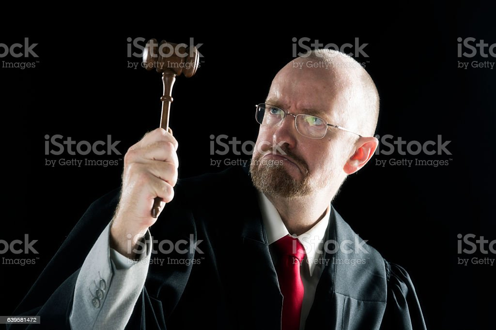 Judge looks at the law hammer in court stock photo