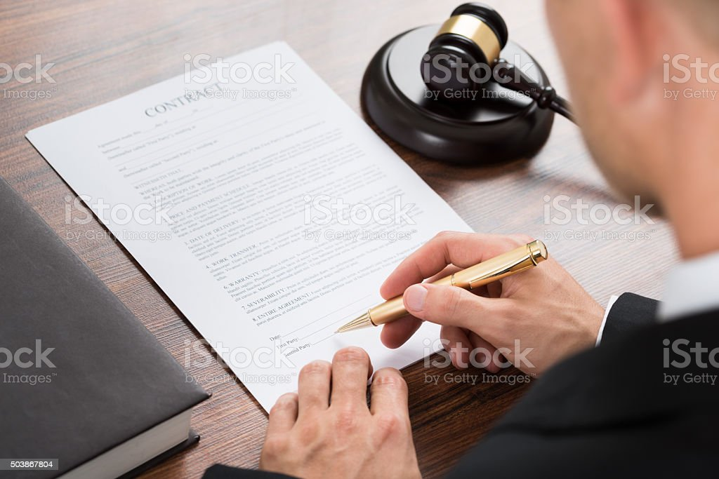 Judge Signing Contract Paper At Desk stock photo