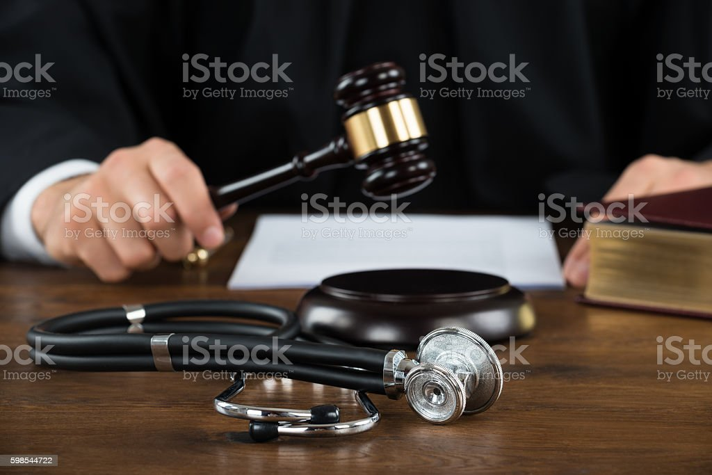 Judge Striking Mallet With Stethoscope At Desk stock photo