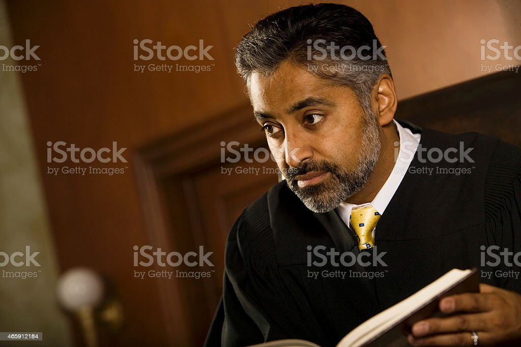 Judge With Book Looking Away In Court Room stock photo