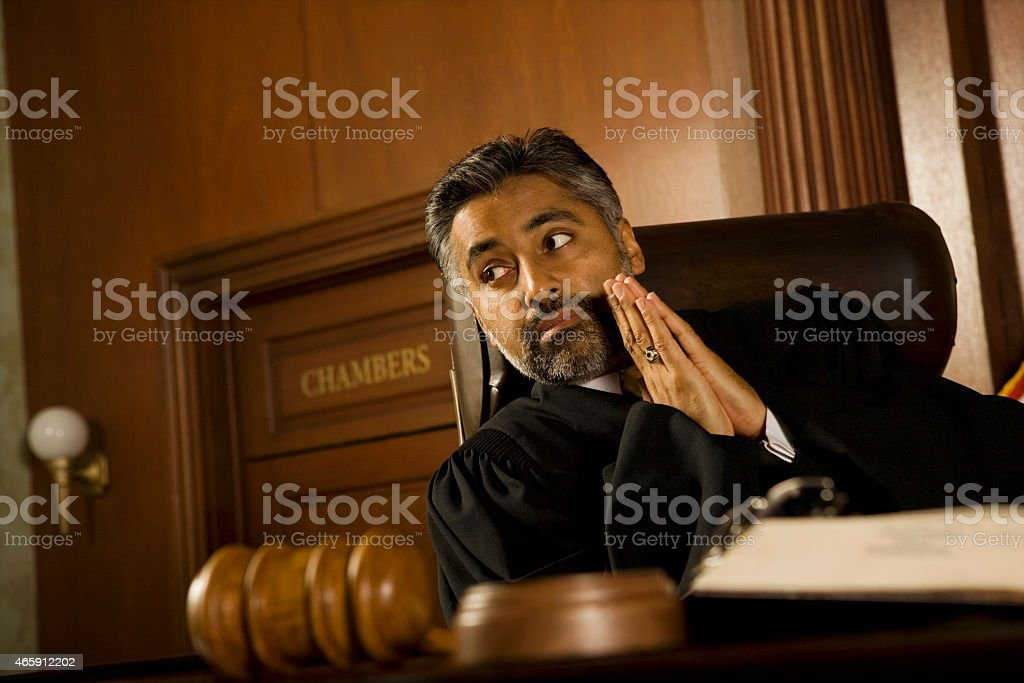 Judge With Hands Clasped Looking Away In Court Room stock photo