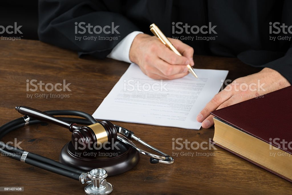 Judge Writing On Document With Mallet And Stethoscope At Desk stock photo