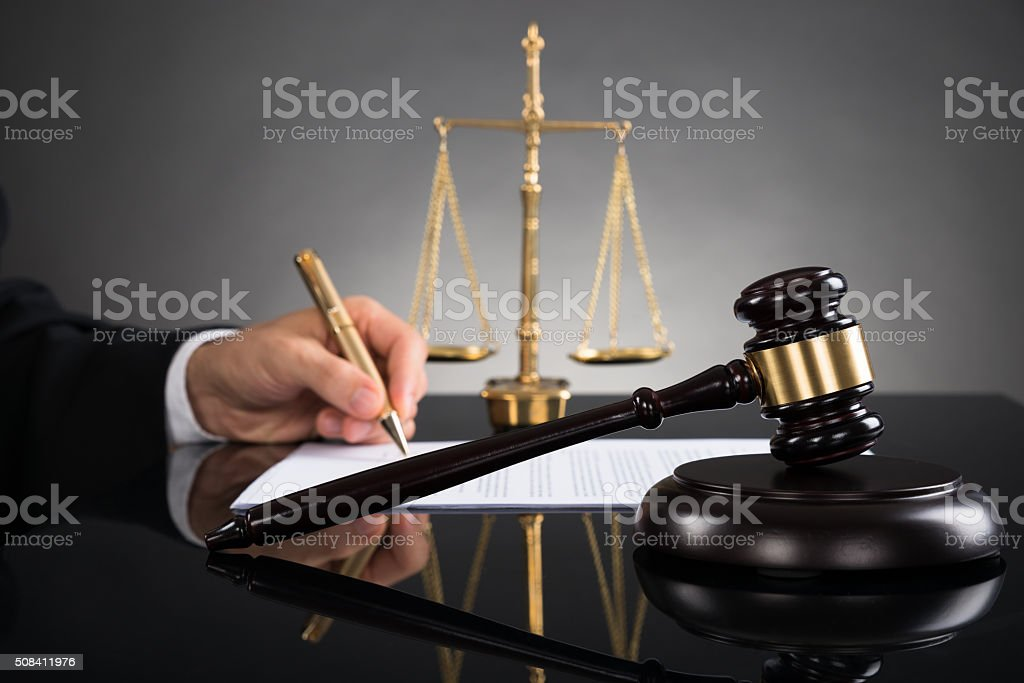 Judge Writing On Paper At Desk stock photo