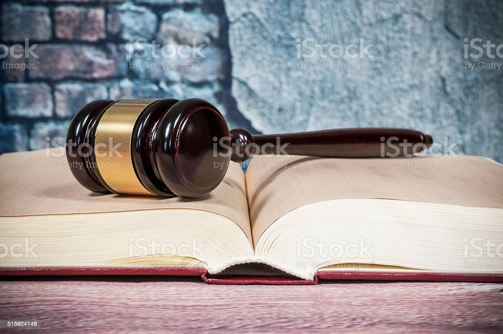 judges gavel and  book on wall background stock photo