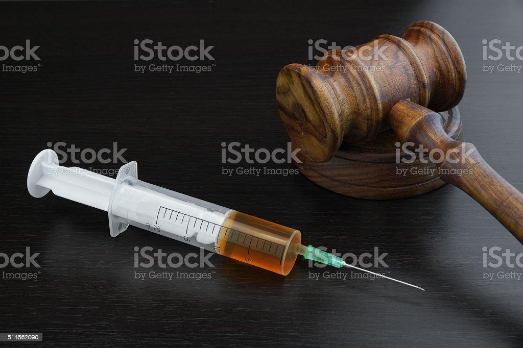 Judges Gavel And Medical Injection Syringe On Black Wooden Backg stock photo