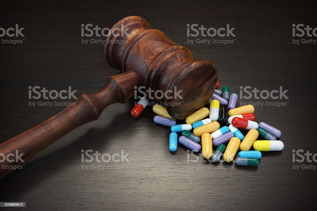 Judges Gavel And Medication On Black Wood Grunge Background stock photo