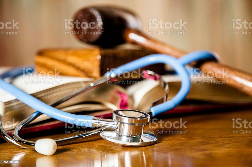 Judge's gavel and stethoscope on court room desk. stock photo