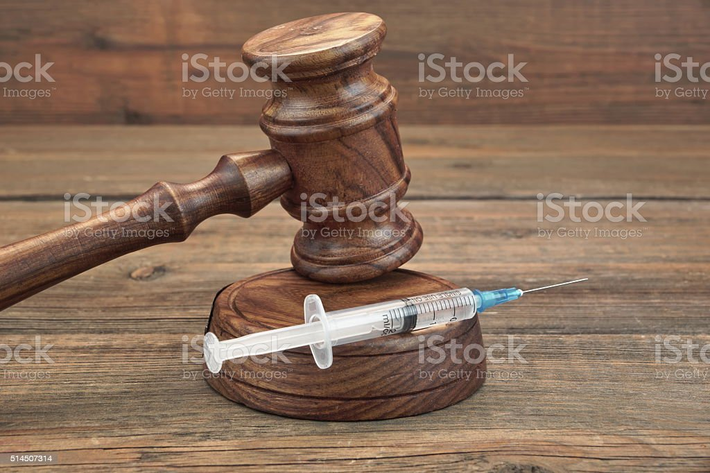 Judges Gavel And Syringe On Brown Wooden Background Close-up stock photo
