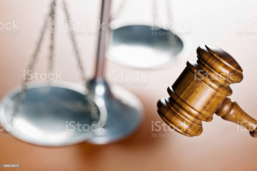 Judge's gavel in front of symbolic scales of justice stock photo
