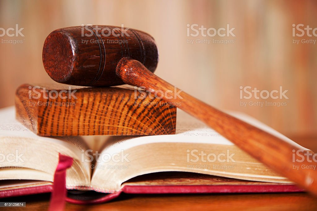 Judge's gavel with book on court room table. stock photo
