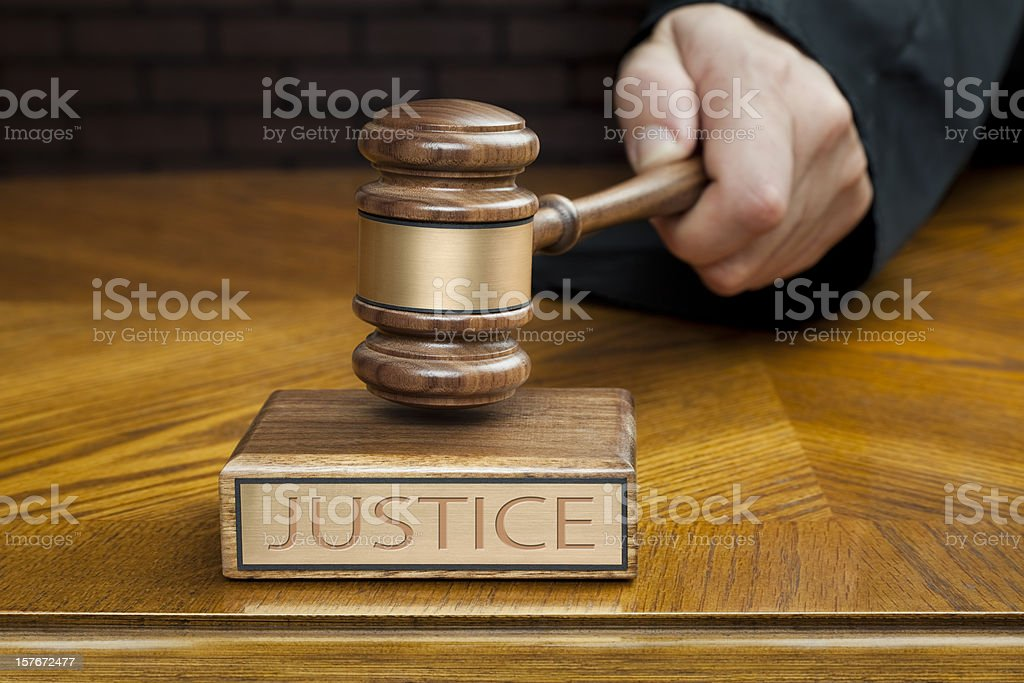Judge's Hand Pounding Gavel To End Courtroom Trial royalty-free stock photo