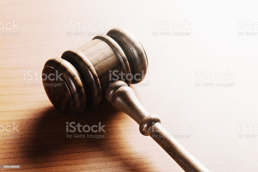 Judge's or auctioneer's gavel on brightly lit wooden desk stock photo