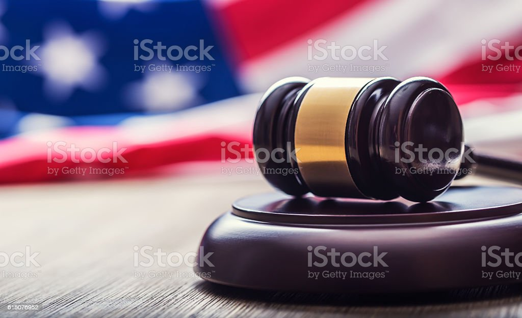 Judges wooden gavel with USA flag in the background. stock photo
