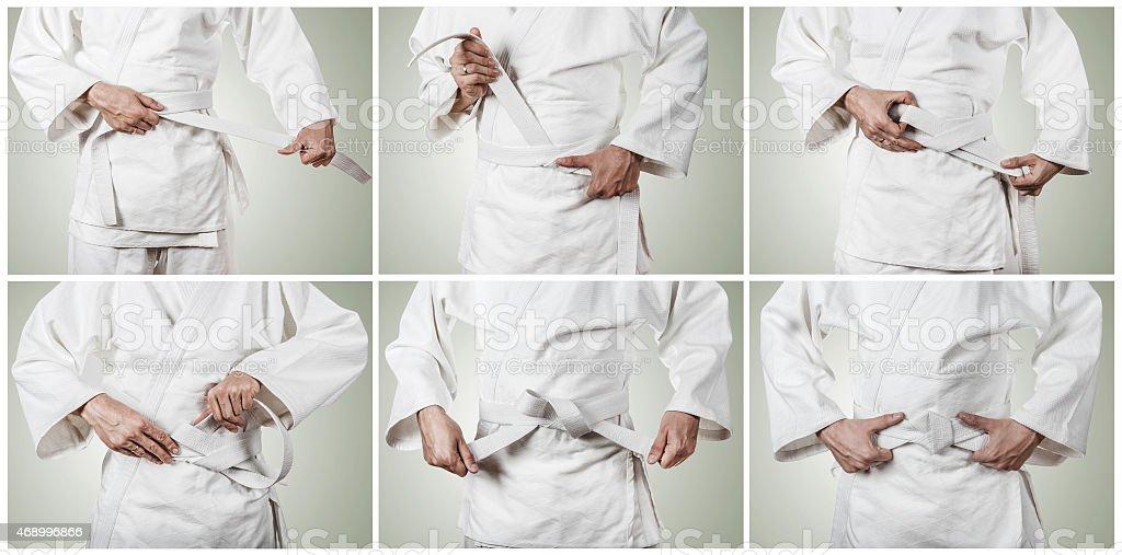 Judoka tying the white belt (obi) stock photo