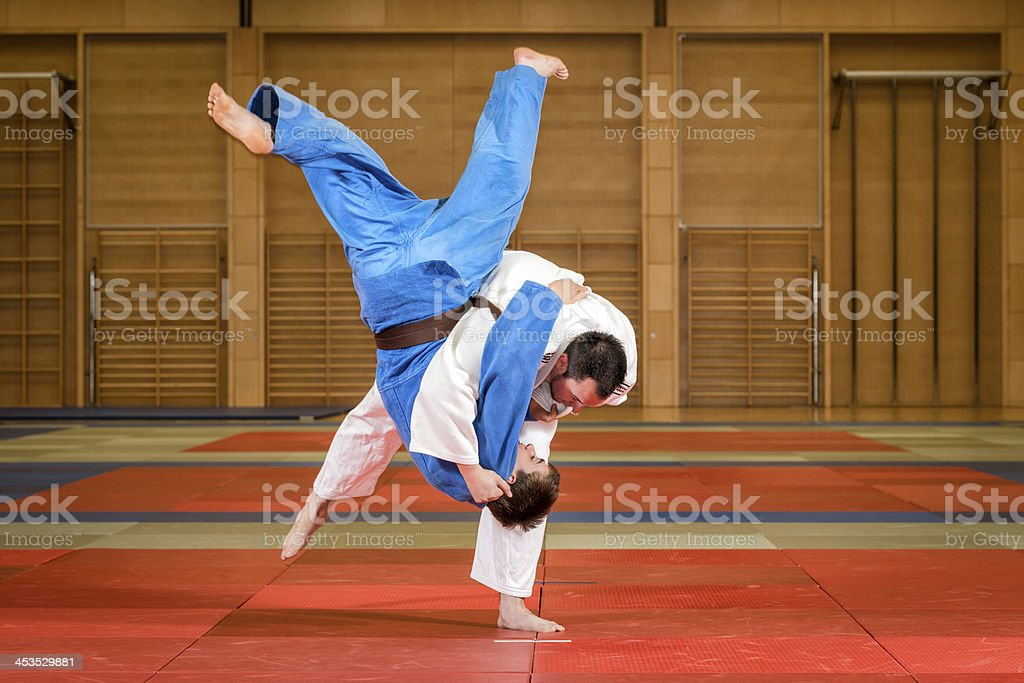 Judokas fighting, one in white, one in blue stock photo