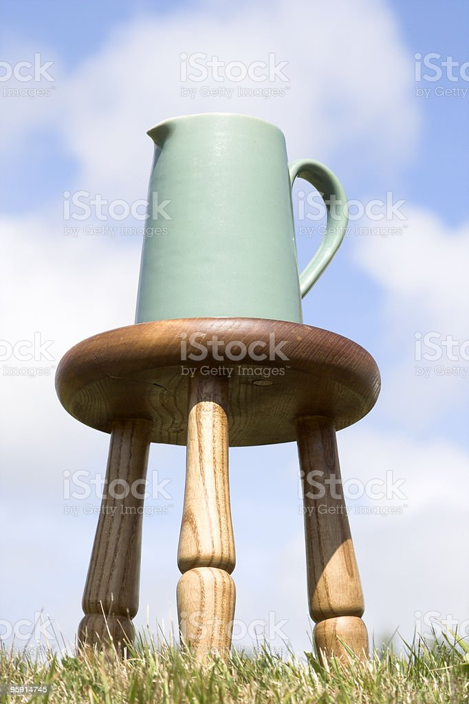 Jug And Milking Stool On Grass stock photo