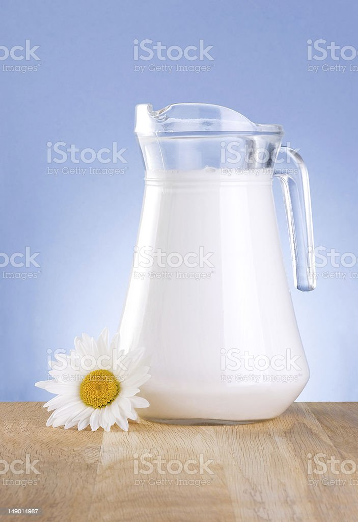 Jug fresh milk and one chamomile flowers is wooden table royalty-free stock photo