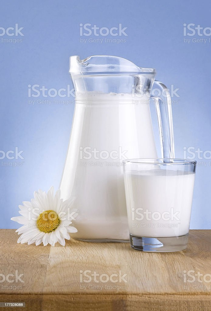 Jug fresh milk, Glass and chamomile flowers is wooden table royalty-free stock photo